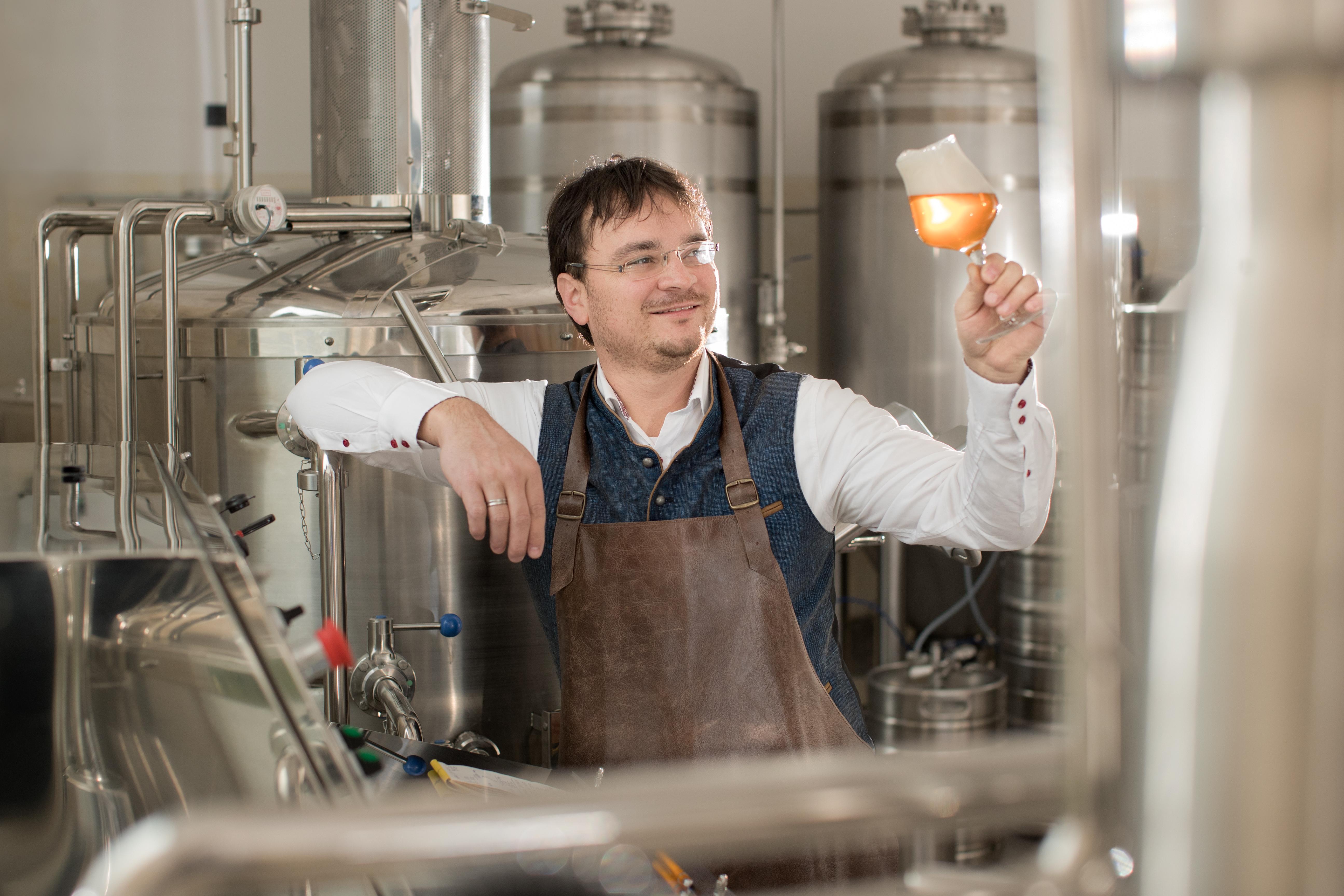 Herr Krammer steht in der Brauerei mit einem Glas Bier